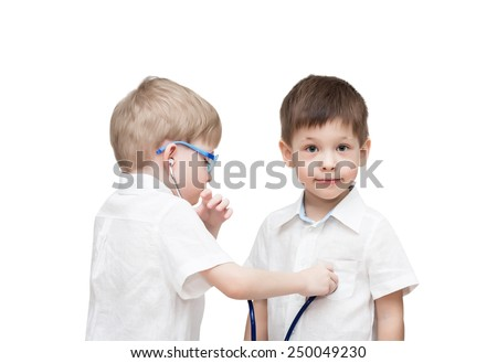 Four-year-old twins boys, in white linen shirts, one through a stethoscope listens to heartbeat of another, isolated on the white