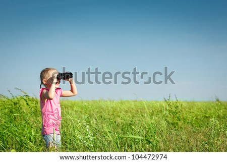 Four years girl in the field looking away through the binoculars - stock photo
