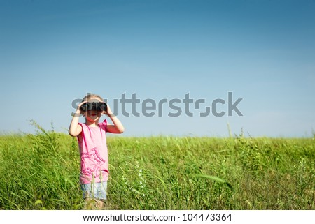 Four years girl in the field looking away through the binoculars at you - stock photo
