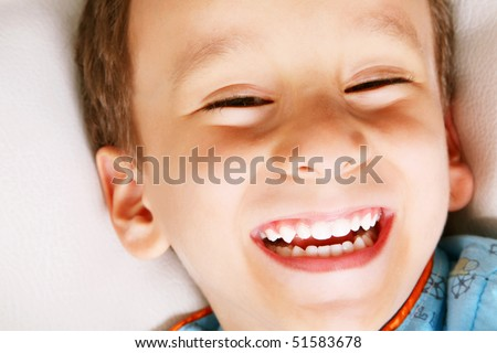 Four years old boy laughing over white background. Happiness concept