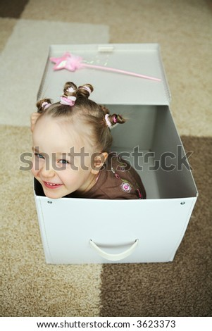 Four years old girl coming out from a carton box