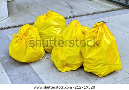 Four yellow garbage bags on the street - stock photo