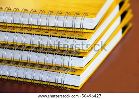four yellow notebooks with ring binding stack on desk closeup
