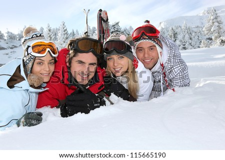 Four young adults laying in the snow - stock photo