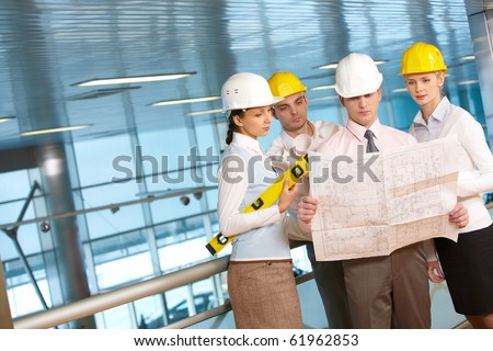Four young architects examining a housing plan - stock photo