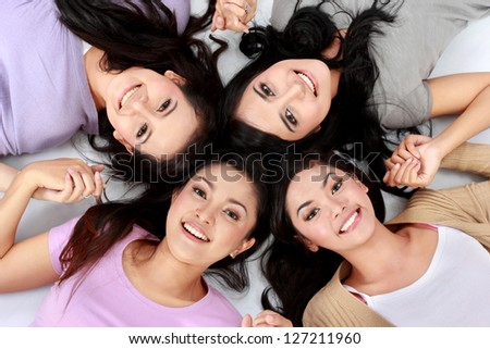 four young attractive asian women relaxing smiling lying on the floor - stock photo