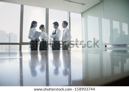 Four young business people standing by conference table - stock photo