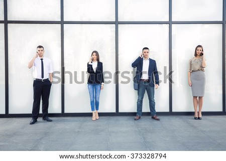 Four young business people talking on mobile phones in front of contemporary office building - stock photo