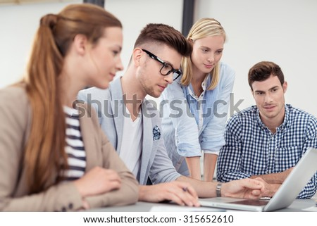 Four Young Businessmen Looking at the Laptop Screen Together While Having a Meeting Inside the Boardroom. - stock photo