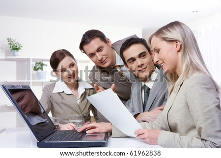 Four young businesswomen sitting at table with a laptop and examining a document