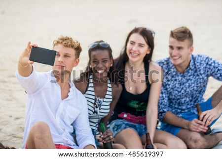 Four young cheerful people taking photo and smiling. Adults make a selfie on a beach.