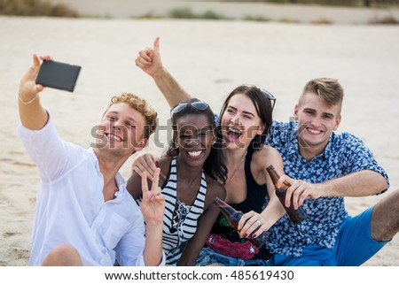 Four young cheerful people taking photo and smiling. Adults make a selfie on a beach and thumb up.