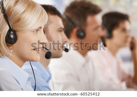 Four young customer service operators sitting in a row and talking on headset.? - stock photo