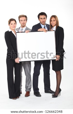 Four young executives holding a framed board left blank for your image - stock photo
