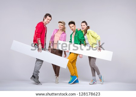 Four young friends holding two empty boards