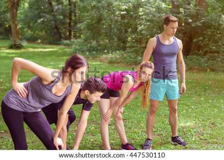 Four young friends in sportswear relaxing after working out in green grassy park standing leaning forwards on their knees as they catch their breath - stock photo