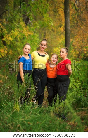 Four Young Girlfriends Hanging Out in the Forest with Autumn Colours