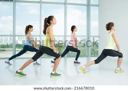 Four young girls doing lunges in the gym - stock photo
