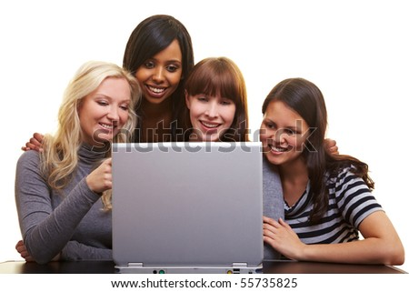 Four young happy woman centered around a laptop - stock photo