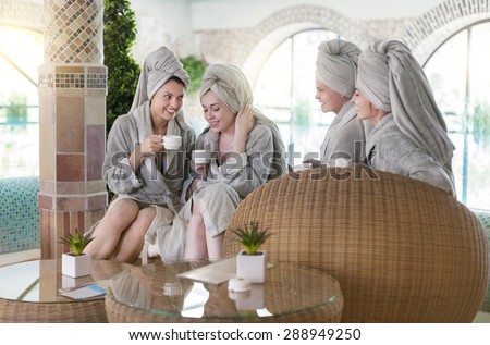 Four young happy women drinking tea at spa resort - stock photo