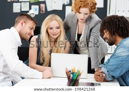 Four young multiethnics busniess people sitting sharing a laptop as they work on a project together - stock photo