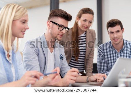 Four Young Office Professionals Watching Something on Laptop Computer on Top of the Table Together - stock photo
