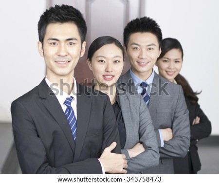 Four young office workers with hands crossed indoors,portrait