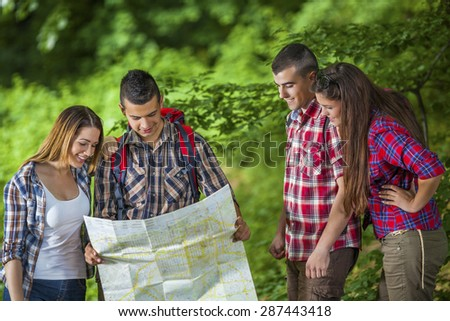 Four young people looking at map while hiking in the forest  - stock photo