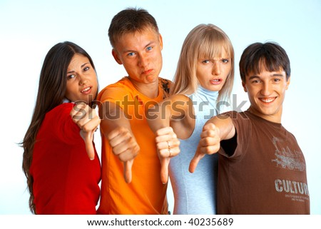 Four young people on white background and giving the thumbs-down sign. - stock photo