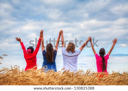 Four young people staying with raised hands at a wheat field at sunset time
