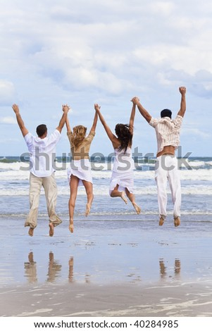 Four young people, two couples, holding hands, having fun and jumping in celebration on a beach - stock photo