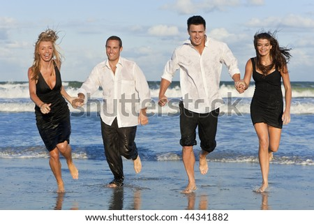 Four young people, two couples, holding hands, having fun and running in the sea on a beach