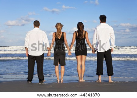 Four young people, two couples, holding hands, looking out to sea on a beach
