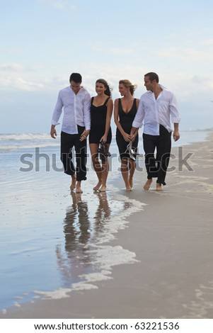 Four young people, two couples, holding hands, looking out to sea on a beach - stock photo