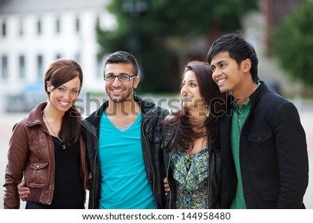 Four young people walking through the town - stock photo