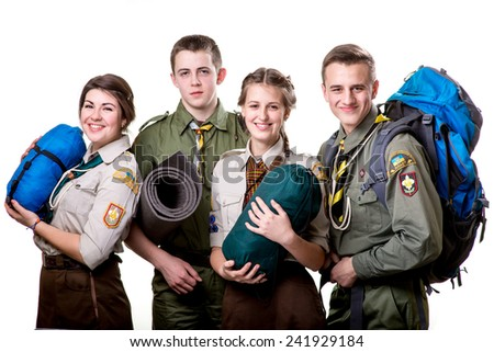 Four young scouts members in uniform with sleeping bags, karemat and backpack isolated on white background - stock photo