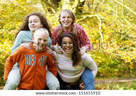 Four young teenager friends playing piggy bag racing game in a park forest during the fall autumn season with yellow trees, having fun, laughing and running together. - stock photo