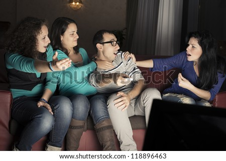 Four young teenager watching tv on a sofa