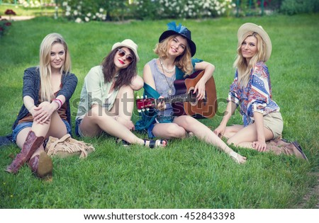 Four young women, girlfriends. Girls wearing boho style. Hippie woman with guitar. Group of women spending time outdoors.