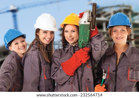 Four yung women wearing work clothes and helmets isolated with work path in front of a construction background. - stock photo