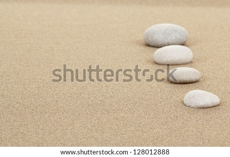 four zen stones in sand as background or backdrop