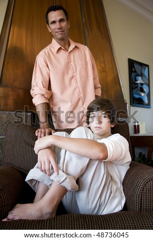 Fourteen year old boy sitting on couch with father standing behind - stock photo