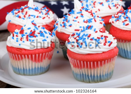 Fourth of july cupcakes on a platter with a flag in background - stock photo