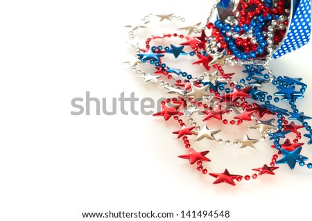 Fourth of July Red, White, and Blue Beads in Star Shapes Flowing out of a Little Bucket on White, Reflective Background with Room or Space for your Words or Text - stock photo