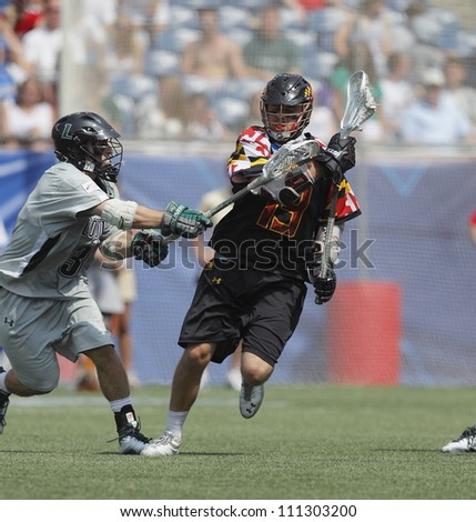 FOXBOROUGH - 28 MAY: Joe Cummings (19) brings the ball to the goal against Chris Layne (3), Loyola, at the NCAA Men's Division 1 Lacrosse Championship game in Foxborough, Massachusetts, 28 May 2012