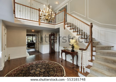 Foyer in luxury home with carpeted stairs.