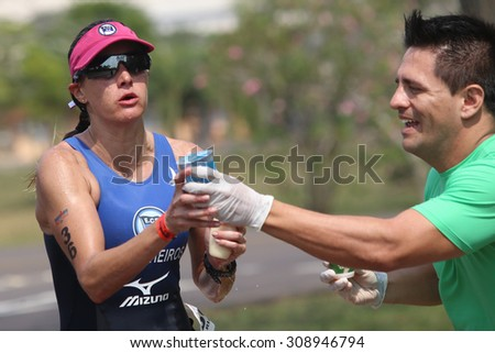 FOZ DO IGUACU, BRAZIL - MAY 30, 2014: Ariane Monticeli grab water from a drink station during the Ironman 70.3 Foz do Iguacu. She won the race - stock photo