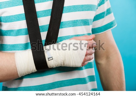 Fractures and dislocations concept. Part body male with hand in bandage. Helpful medication for painful palm arm of young man.