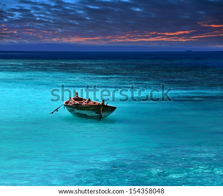 fragile boat in a stormy sea - stock photo