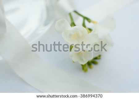 Fragile freesia flower straw on white table cloth with glass vase  - soft dreamy wedding invitation card